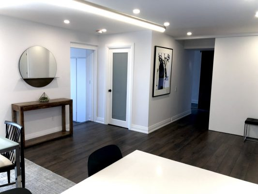 Image depicts hallways in a home with white painted walls.