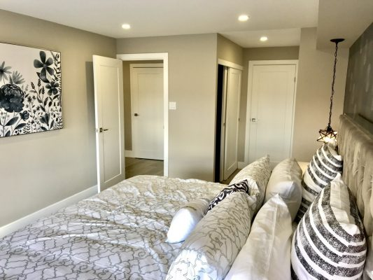 Image depicts a bedroom with newly painted light grey walls.